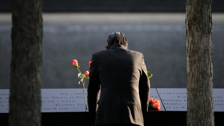 A man stands at the edge of a waterfall pool during a ceremony at ground zero in New York, Monday, Sept. 11, 2017. Holding photos and reading names of loved ones lost 16 years ago, 9/11 victims' relatives marked the anniversary of the attacks at ground zero on Monday with a solemn and personal ceremony. (AP Photo/Seth Wenig)
