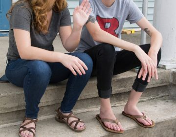 Two students sit on the front porch at one of the three