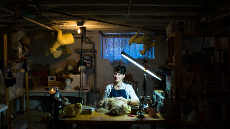 Beth Beverly works in her studio where she makes hats, jewelry and home decor items with parts of dead animals. (Paige Pfleger/WHYY)