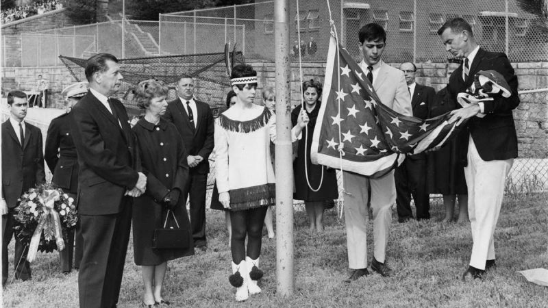 A flag that draped casket of John M. Cole, Jr., a Roxborough High School graduate who died in Vietnam, is unfurled during a May 26, 1967, memorial service on the school athletic field by Paul Cottone, student body president, and Robert Bunch (right), a faculty advisor. Cole's parents, Mr. and Mrs. John M. Cole, are at left. Their daughter, Donna, a member of the school drill team, waits to raise the flag. (Charles T. Higgins / Courtesy of George D. McDowell Philadelphia Evening Bulletin Collection, Temple University Libraries)