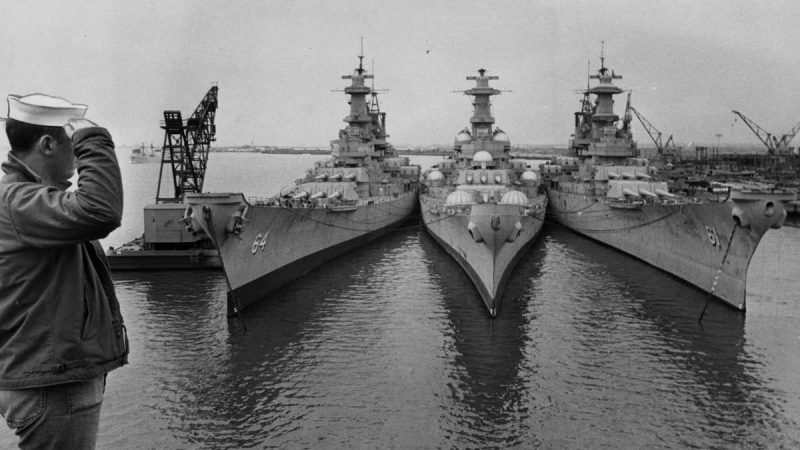 Sailor Will Schroeder, of Providence, R.I., salutes the three battleships in the mothball fleet at the Philadelphia Naval Base that are being considered for Vietnam war duty. Ships are (from left) the Wisconsin, the New Jersey, and the Iowa, c. April 1967. (Courtesy of George D. McDowell Philadelphia Evening Bulletin Collection, Temple University Libraries)