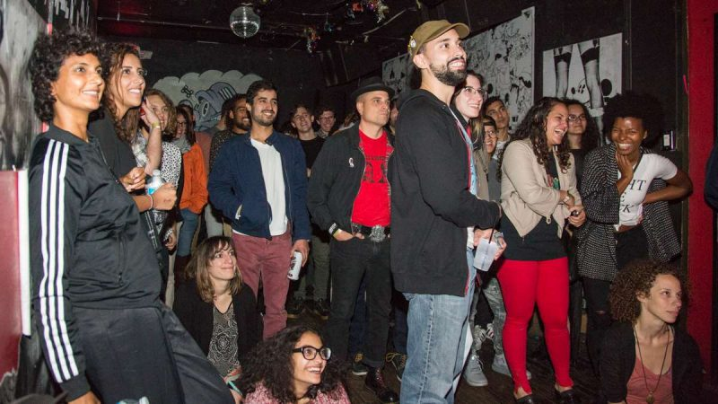 Attendees of the first annual YallaPunk Festival listen and laugh as comedy headliner Aron Kader closes out the day at The Barbary. (Emily Cohen for WHYY)