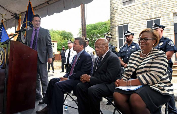 Activist Patrick Duff addresses the crowd at the September 2016 press conference in front of the Walnut Street home where Martin Luther King, Jr. spent time as a seminary student; seated are, from left to right: Rep. Donald Norcross; Rep. John Lewis; and Camden Mayor Dana Redd.  (April Saul/for WHYY)