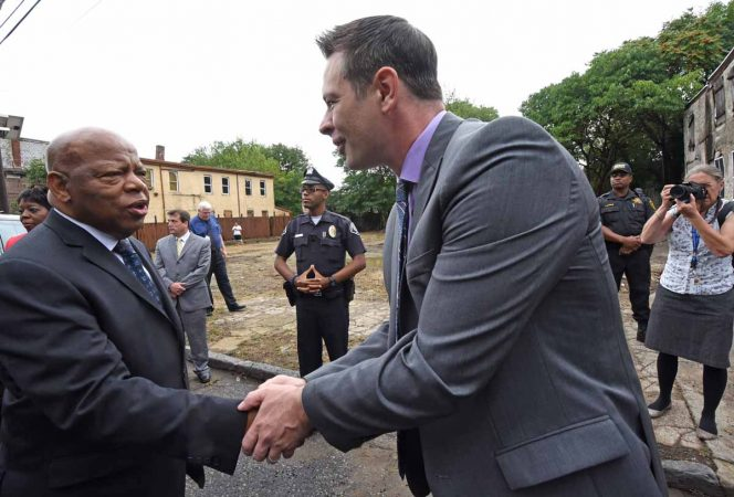 Activist Patrick Duff shakes hands with Rep. John Lewis at the September 2016 press conference in front of the Walnut Street home where Martin Luther King, Jr. spent time as a seminary student.  (April Saul/for WHYY)