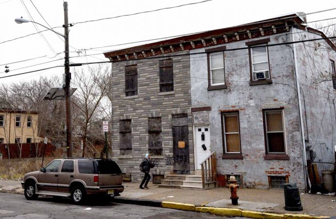 At left; the rowhouse with boarded-up windows at 753 Walnut Street where Martin Luther King, Jr. spent time as a seminary student.  (April Saul/for WHYY)