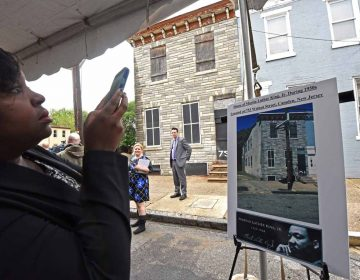 At the September 2016 press conference to announce the preservation of the house at 753 Walnut Street where Martin Luther King, Jr. stayed, a woman photographs a poster; the house is in the background.  (April Saul/for WHYY)