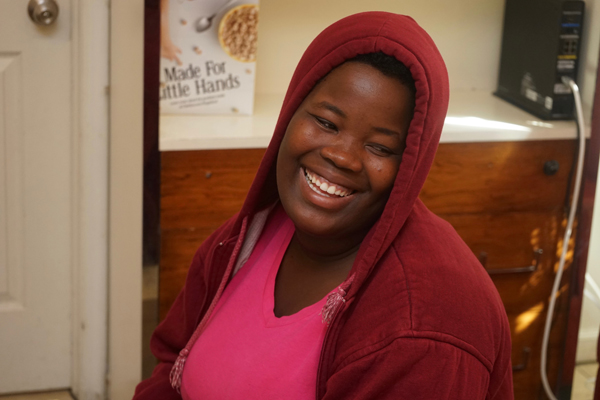 A smiling Tatiana Angama in a pink shirt and maroon hoodie