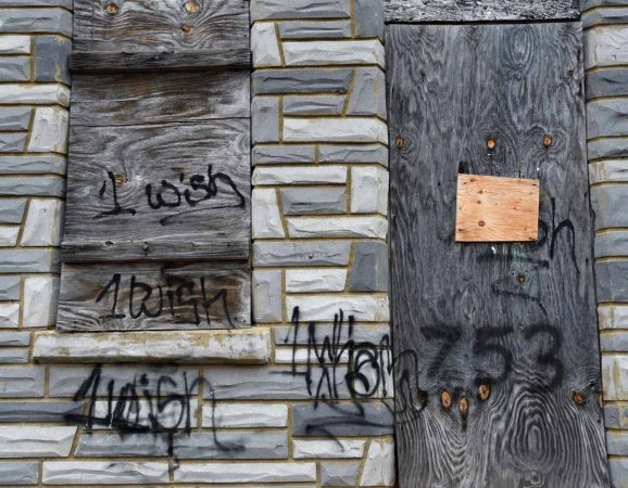 Graffiti on the front of the house at 753 Walnut Street in Camden where Martin Luther King, Jr. stayed as a seminary student before it was removed for a September 2016 press conference.  (April Saul/for WHYY)