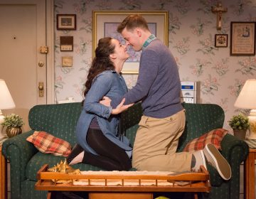 Two people embrace, kneeling, facing towards each other on a couch; scene from a play, likely in song