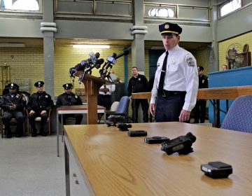 Lt. Tom McLean stands near a table, a half-dozen body camera options are displaued; officers sit and stand in the background