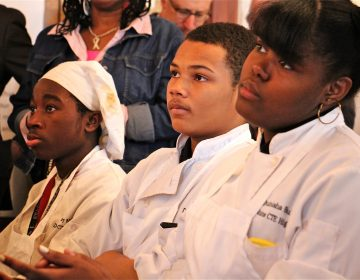 Students dressed in chef's whites listen during an assembly.
