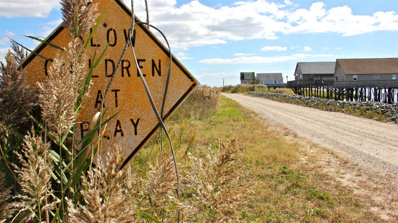 An overgrown sign warns of children at play along the dirt road that leads to the deserted homes of Bay Point.