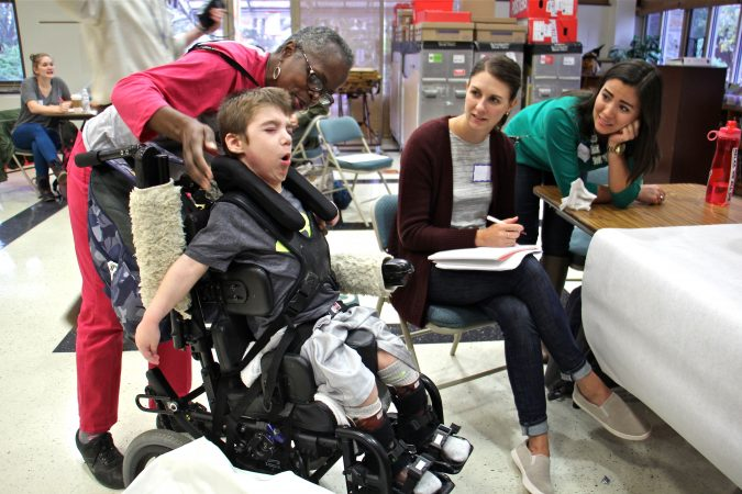 Janice Barbour (left) tends to Carter, 7, who often gets his arms stuck behind the armrests on his wheelchair. Temple students Sarah Forsythe (right) and Ashley Bauer work to design attachments that will prevent that from happening