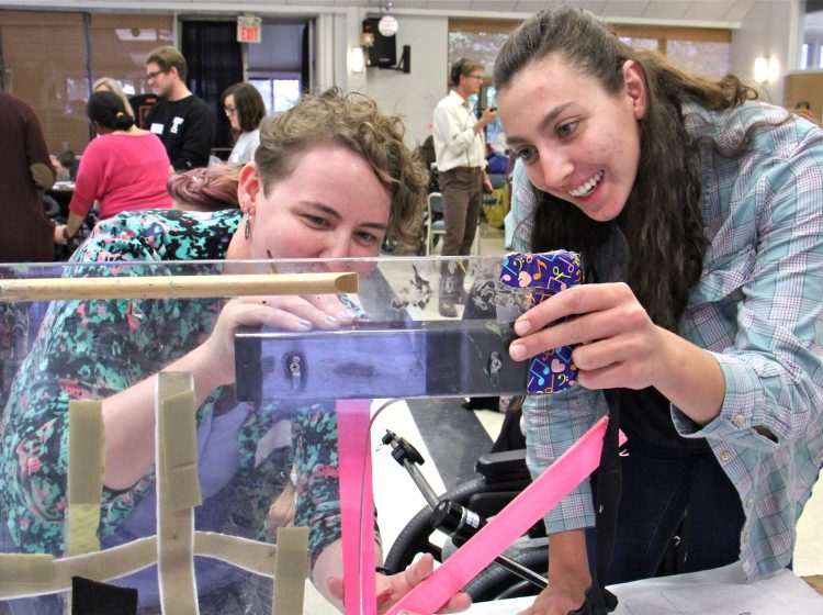 Rachel Adler (left) and Nicole Maximowicz take measurments before designing a wheelchair tray that will protect Ana's communication device