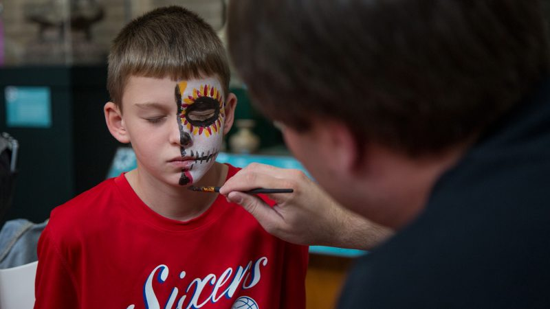 A man paints half of a boy's face to look like a skull