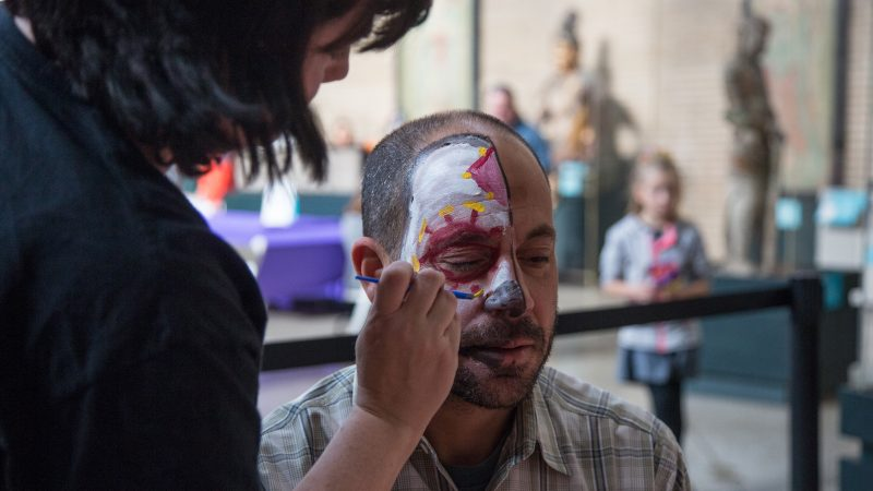 A woman man paints half of a man's face to look like a skull