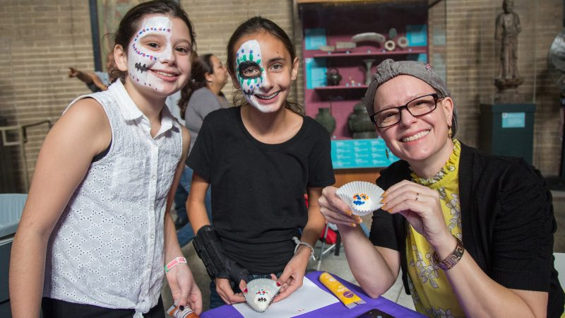 children in skull face paint hold up their decorated sugar skulls