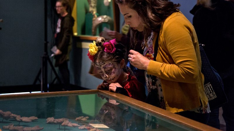 A mother and child look at artifacts in a glass case at Penn Museum. The child's face is painted like a skull.
