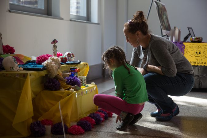 A mother and daughter inspect a Day of the Dead altar at Penn Museum