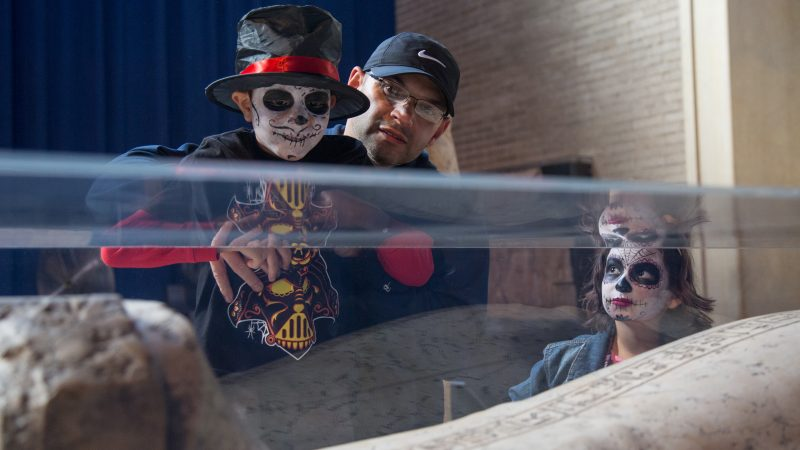 children in skull face paint look at a mummy in a glass case