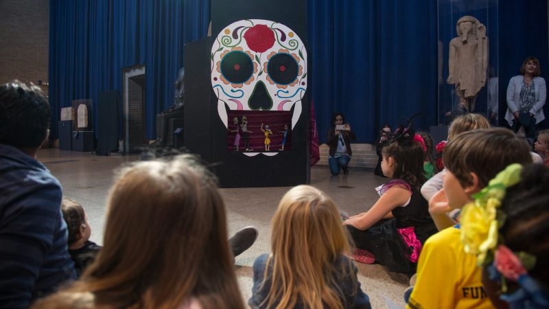 Children and adults gather to watch a marionette puppet show explaining the celebrations around Dia de los Muertos at Penn Museum's annual Day of the Dead celebration October 28, 2017. (Emily Cohen for WHYY)