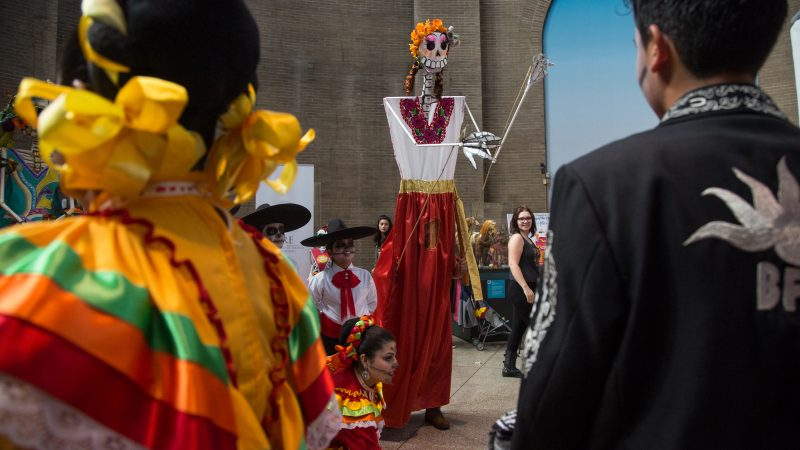 A large skeleton puppet dances with traditional Mexican dancers at a day of the dead celebration