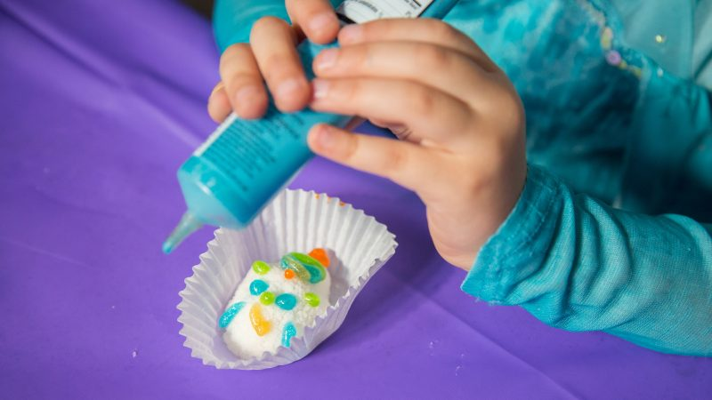 a child applies blue icing to a sugar skull
