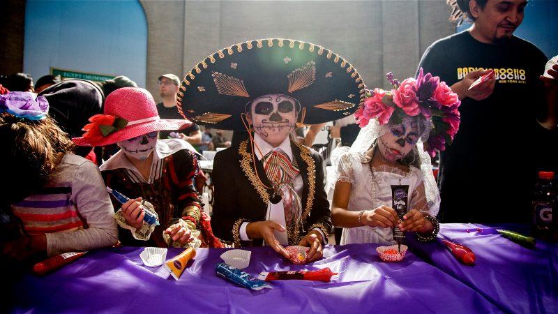 Costumed children in skull face paint decorate sugar skulls