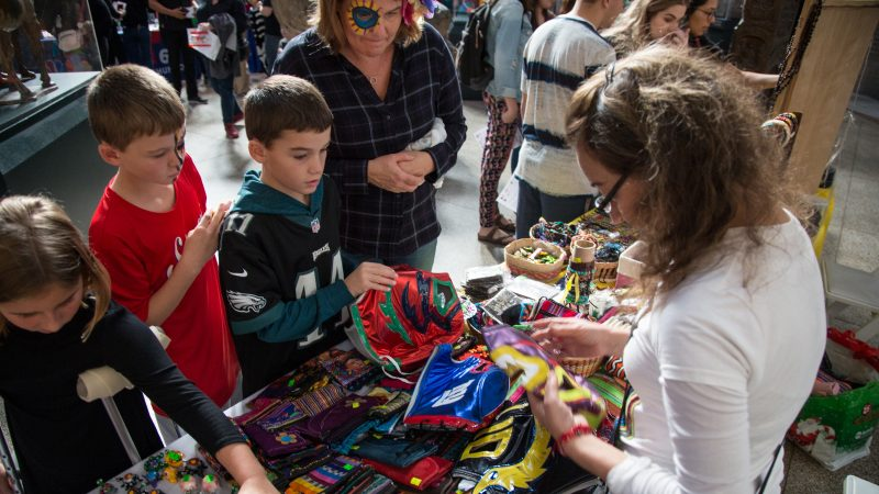 Children sort through lucha libre masks, used by Mexican professional wrestlers, for sale at a day of the dead celebration
