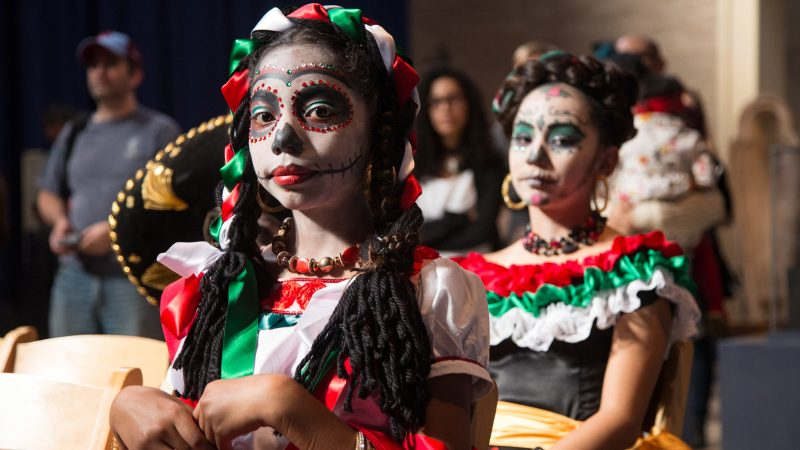 Young girls in red white and green costumes with faces painted like skulls prepare to dance at a Day of the Dead Celebration