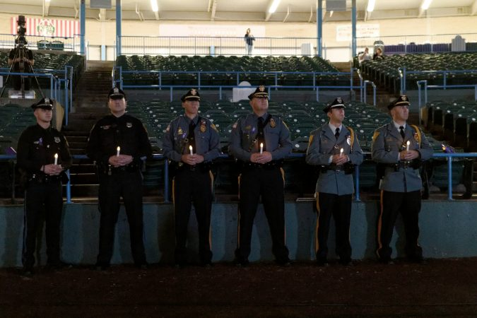 Police officers hold candles during the Regional Candlelight Vigil on October 14, 2017, at Camden Waterfront Stadium. (Bastiaan Slabbers for WHYY)