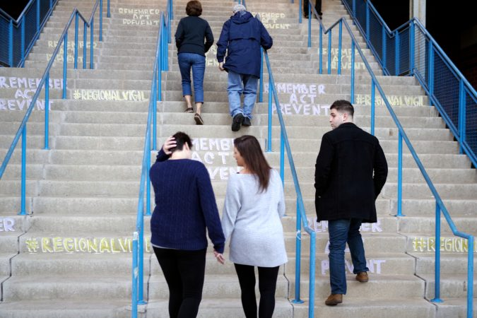 Attendees climb the stairs at Camden Waterfront Stadium for a the Regional Candlelight Vigil for the victims of drug addiction. (Bastiaan Slabbers for WHYY)