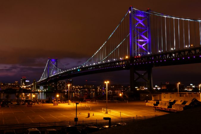 The ben Franklin Bridge is illuminated with purple lights to call attention to overdose victims during the Regional Candlelight Vigil at Camden Waterfront Stadium. (Bastiaan Slabbers for WHYY)