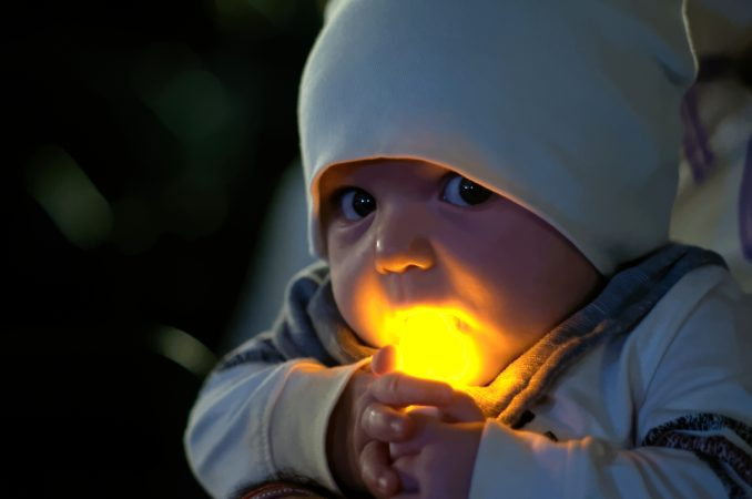 Five-month-old Paxton Perrone holds a battery operated candle at the Regional Candlelight Vigil fro victims of addiction at Camden Waterfront Stadium on October 14, 2017. (Bastiaan Slabbers for WHYY)