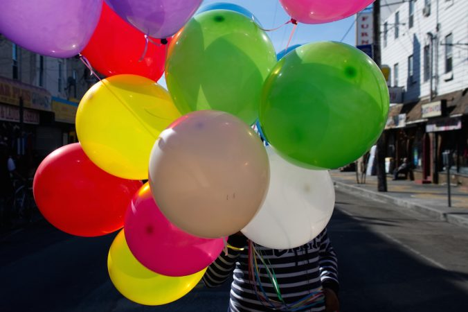 Balloons obscure the face of a girl as she crosses the street during Philly Free Streets event, Saturday, Oct. 28, 2017. (Bastiaan Slabbers for WHYY)