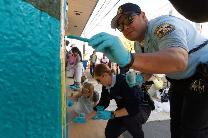 Police officers join kids as they take part in the creation of a mural during Philly Free Streets event, Saturday, Oct. 28, 2017. (Bastiaan Slabbers for WHYY)