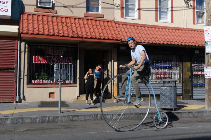 Bystanders watch as a man on a penny-farthing bike rolls past during Philly Free Streets, Saturday, Oct. 28, 2017. (Bastiaan Slabbers for WHYY)