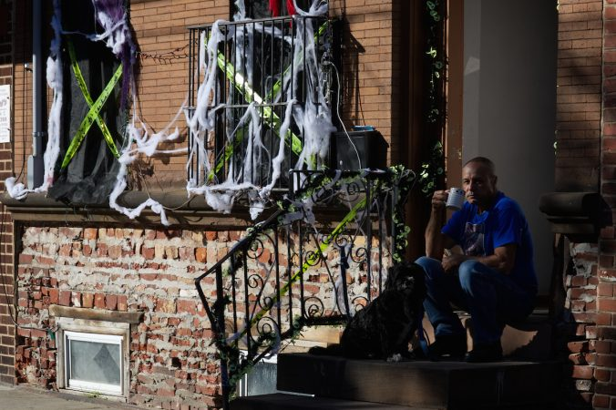 From his stoop a resident watches human-powered traffic go past during Philly Free Streets, Saturday, Oct. 28, 2017. (Bastiaan Slabbers for WHYY)