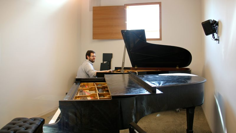 A piano tuner works in one of the practice rooms at the New Music Building. (Emma Lee/WHYY)