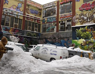 A warehouse covered in large grafiti art; In the foreground, a man shovels snow.