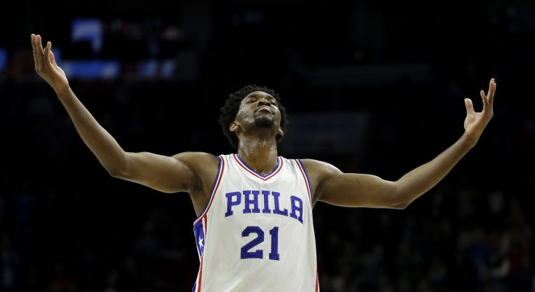 7 feet 2 inch- basketball star, Joel Embiid, number 21, in Sixers uniform, arms spread wide, looking up
