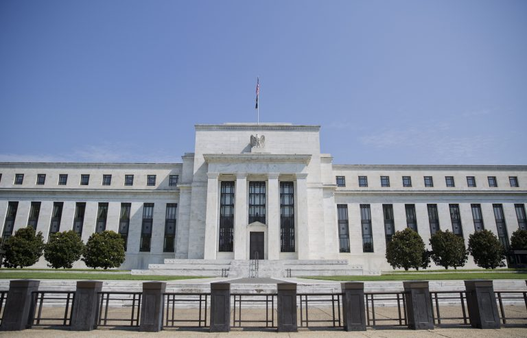 The Federal Reserve Building; white columns, black fencing against a blue sky