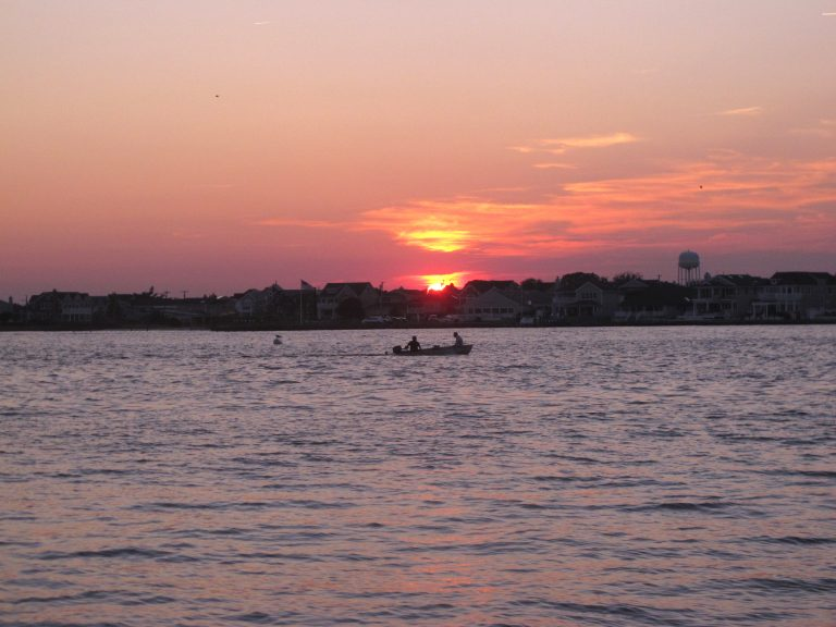 Sunset, a pink sky, and a small boat on Barnegat Bay