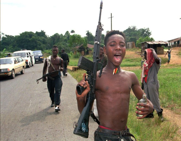 A child soldier; intoxicated and shirtless, holds a rifle