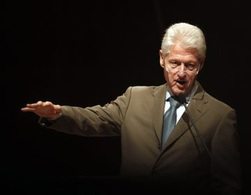 Bill Clinton, olive suit, arm outstreched gesturing, black background