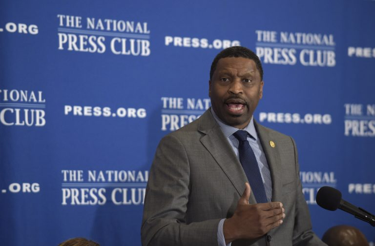 A man in a suit speaks in front of a blue, National Press Club background