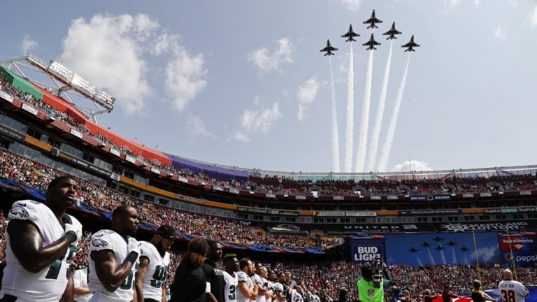 In formation and against a blue sky, members of the U.S. Air Force Thunderbirds fly overhead while Eagles players look on, hands on their hearts, during the national anthem