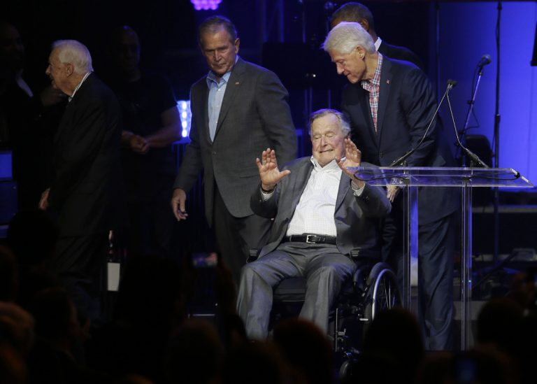 President George H.W. Bush in a wheelchair, hands up, palms out, leaving a stage; President Bill Clinton pushes Bush, Sr.; President George W. Bush walks off stage, looking back to his father
