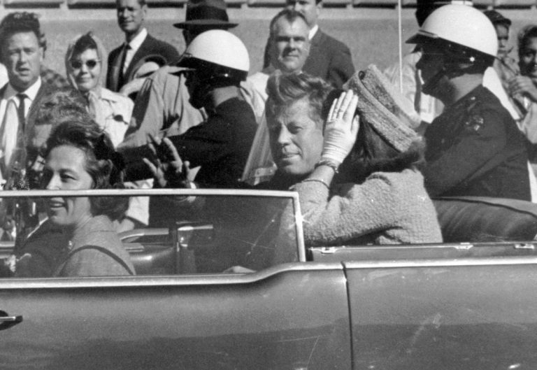 Black and white photo of Mr. and Mrs. JFK in the limousine, moments before the assassination