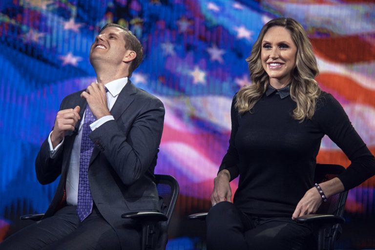 Eric Trump, (left), fixes his tie as Lara Trump, (right), smiles